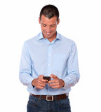 Handsome adult male texting with his cellphone. Portrait of a handsome adult male on blue shirt and jeans texting with his cellphone while standing on isolated Royalty Free Stock Photo