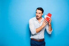 Handsome adult man on blue background with christmas gift Stock Image