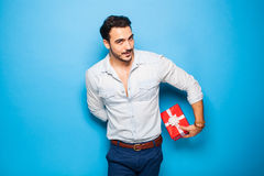 Handsome adult man on blue background with christmas gift. Cute guy hiding a christmas gift behind him on blue background Royalty Free Stock Photo