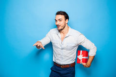 Handsome adult man on blue background with christmas gift. Handsome man hiding a christmas gift behind him on blue background Stock Photography