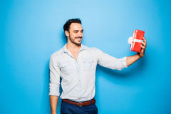 Handsome adult man on blue background with christmas gift Stock Photo