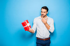 Handsome adult man on blue background with christmas gift Royalty Free Stock Image