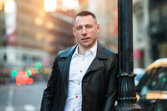 Handsome adult man in the city wearing casual outfit with black leather jacket and white t-shirt. stock photography