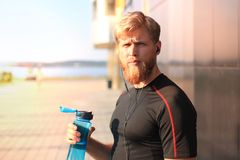 Handsome adult man drinking water from fitness bottle while standing outside, at sunset or sunrise. Runner. Handsome adult man drinking water from fitness royalty free stock image