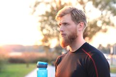 Handsome adult man drinking water from fitness bottle while standing outside, at sunset or sunrise. Runner. Handsome adult man drinking water from fitness stock photo