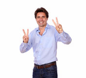 Handsome adult man gesturing victory sign. Portrait of a handsome adult man gesturing victory sign on isolated background Royalty Free Stock Images