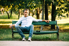 Handsome adult man sitting on bench Royalty Free Stock Images
