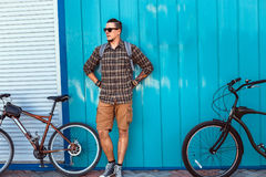 Handsome Adult Man In Sunglasses Stands With A Bicycle Along A Blue Wall Daily Lifestyle Urban Resting Concept. A young male traveler in sunglasses and with a stock photos