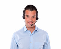 Handsome adult man talking with earphone. Portrait of a handsome adult man talking with earphone while smiling at you on isolated studio Royalty Free Stock Image