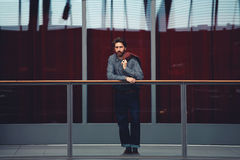 Handsome adult man went to the balcony to get some fresh air. Full length portrait of stylish mature man standing interior beautiful big hall with glassy red royalty free stock photos