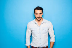 Handsome adult and masculine man on a blue background Royalty Free Stock Images