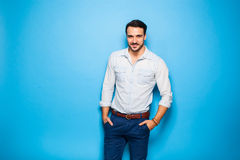 Handsome adult and masculine man on a blue background Stock Photography