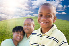 Handsome African American Boy with Parents. Handsome African American Boy with Proud Parents Standing Over Clouds, Sky and Arched Horizon of Grass Field Stock Image