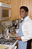 Handsome African-American businessman in kitchen. Handsome African-American businessman cooks dinner after work Royalty Free Stock Image