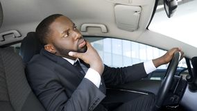 Handsome African-American businessman looking in car mirror, having doubts stock photos
