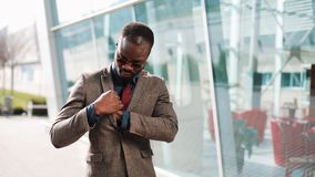 Handsome African American businessman waiting for a message on his smartphone. Black man standing near the office. Building. Business, people, communication stock video footage