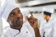 handsome african american chef pointing up stock photography