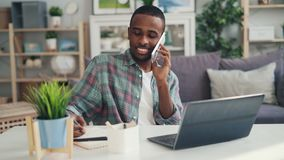 Handsome African American guy self-employed person is working with laptop at home and talking on mobile phone sitting at