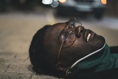 Handsome African-American guy with street glasses. Black man serious. Close up Handsome African-American guy with glasses on the street. Portrait black man royalty free stock photo