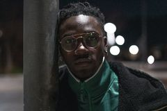 Handsome African-American guy with street glasses. Black man serious. Close up Handsome African-American guy with glasses on the street. Portrait black man royalty free stock photography