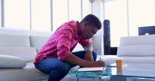 Handsome African american male executive writing on a diary in modern office 4k. Side view of handsome African american male executive writing on a diary in stock video
