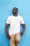 Handsome african american man against blue wall and looking up Stock Images