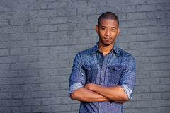 Handsome african american man in blue shirt standing by gray wall Royalty Free Stock Photo