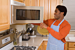 Handsome African-American man cooks in kitchen Stock Image