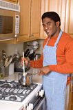 Handsome African-American man cooks in kitchen Royalty Free Stock Image