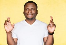 Handsome African American man crosses fingers, closes eyes, anticipate hearing good news. Handsome African American man crosses fingers, closes eyes, anticipate royalty free stock image