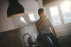 Handsome african american man drinking coffee in kitchen stock image