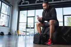 Handsome african american man in earphones sitting in tyre and using smartphone. In gym royalty free stock images