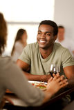 Handsome African-American man with his girlfriend. Handsome young African-American men holding hands with his girlfriend in a restaurant Stock Photo