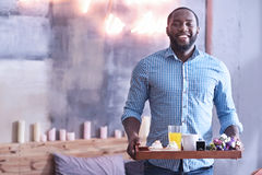 Handsome African American man holding breakfast tray in the bedroom. Delightful from being in love. Charming delightful inspired African American man standing in Royalty Free Stock Image