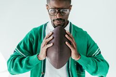 Handsome african american man holding rugby ball. Isolated on white stock photos