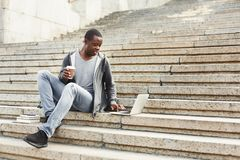 Handsome african-american man with laptop and coffee outdoors. Serious african-american man with laptop and take away coffee sitting on stairs. Casual student Royalty Free Stock Photography