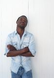 Handsome african american man leaning against white wall outdoors Stock Photo