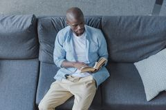 Handsome african american man reading book. At home royalty free stock photo