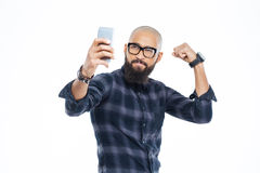 Handsome african american man showing biceps and making selfie. Handsome hairless african american man with beard showing biceps and making selfie Stock Photos