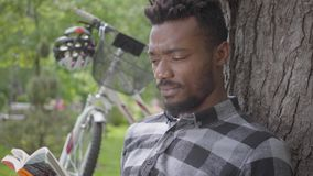 Portrait confidient cute handsome African American man sitting near his bicycle under an old tree in the park reading a stock video