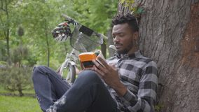 Portrait handsome confidient African American man sitting near his bicycle under an old tree in the park reading a book stock footage