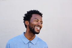 Handsome african american man smiling by white wall Stock Image