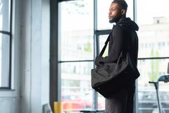 Handsome african american man in sportswear holding bag and looking away. In gym stock photos
