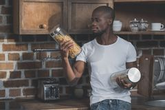 Handsome african american man standing in kitchen and choosing between two jars with raw royalty free stock photo