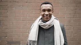 Handsome African American man wearing a coat and a scarf is smiling toward camera. Handheld slow motion portrait shot stock video
