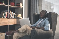 Handsome African american man wearing headphones using laptop. At home stock photo