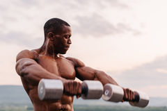 Handsome african american muscular man lifting dumbbells against the sunset sky background Stock Photos