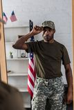 Handsome african american soldier in camouflage clothes posing. By the mirror royalty free stock photography