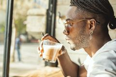 Handsome young African American drinking coffee with milk stock photos