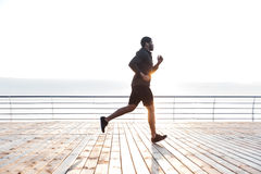Handsome african american young sportsman running on pier Royalty Free Stock Photos